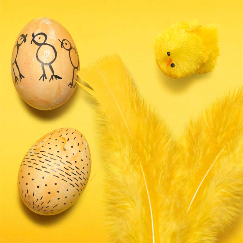 Påskpyssla med att målaägg och sätta fjädrar i påskris